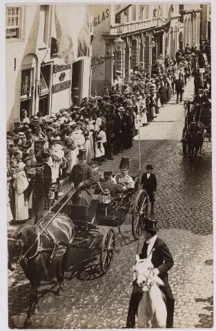 042623 - Optocht in de Heuvelstraat omstreeks 1910. Gezien de vlaggen aan de gevels zou het verband kunnen houden met de verjaardag van een lid van het Koninklijk Huis of ter gelegenheid van een tentoonstelling. Rechts op de voorgrond, gezeten op een schimmel, garde d'honeur Theo Kerstens