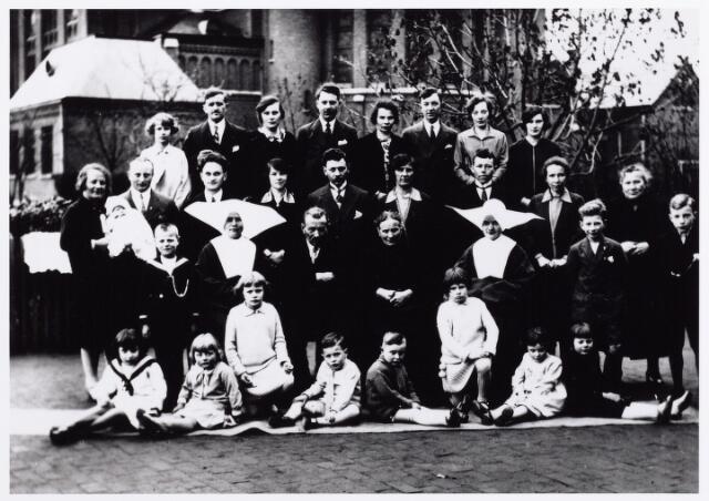 011989 - De familie Van Nunen-Aertse gefotografeerd in 1930 achter de kerk van de Hoefstraat. Johannes Cornelis van Nunen werd geboren te Tilburg op 22.4.1865 als zoon van Peter van Nunen en Maria Catharina van de Sande. Hij trouwde er op 2.5.1888 met Adriana Aertse geboren te Oosterhout op 22.9.1866 dochter van Willem Aertse en Cornelia Lambregts. J.C. van Nunen was wever en woonde aan de Houtstraat. Hij overleed te Tilburg op 5.3. 1941. Zijn vrouw overleed aldaar op 4.12.1935.   De kinderen op de eerste rij zijn van links naar rechts. N.N., Jeanne Lemmens, Corrie Mommers, Mart Mommers (later frater Cesarius) , Jan Somers, Ria Mommers, Corrie Somers (later zuster Leonarda) en Jeanne de dochter van Willem van Nunen.   Op de volgende rij van links naar rechts: Sjef Lemmens, Francisca van Nunen geboren Tilburg 12.11.1897, zij was 40 jaar in het klooster onder andere in het mgr. Mutseartsoord te Venlo, Jan Cornelis van Nunen en zijn vrouw Adriana Aertse, Henrica van Nunen, geboren Tilburg 17.9.1909 als zuster Alphonsa overste te Baak, Jan van Nunen Willemzn. en Jan Mommers (later frater Casimiro).   Op de volgende rij van links naar rechts Catharina Lemmens-van Nunen geboren Tilburg 26.7.1900 met zoontje Rien Lemmens, haar man Marinus Lemmens, Bernardus van Nunen geboren Tilburg 22.9.1904, zijn vrouw Anna van Dongen, Willem van Nunen geboren Tilburg 14.2.1892, zijn vrouw Johanna van Pelt, Johannes Mommers, zijn vrouw Petronella van Nunen geboren Tilburg 27.1.1889 en N.N.  Op de laatste rij van links naar rechts Jo Mommers, Laurentius van de Put en zijn vrouw Maria van Nunen geboren Tilburg 5.12.1894, Leonardus Somers en zijn vrouw Cornelia van Nunen geboren Tilburg 22.5.1896, Adrianus Schoenmakers en zijn vrouw Anna van Nunen geboren Tilburg 13.8.1906 en Josephina van Nunen geboren Tilburg 4.11.1911. Ook zij trad in het klooster en was later als zuster Madeleine hoofd van een kleuterschool. Op de foto ontbreekt zoon Martinus van Nunen geboren Tilburg 18.7.1893 en zijn 
