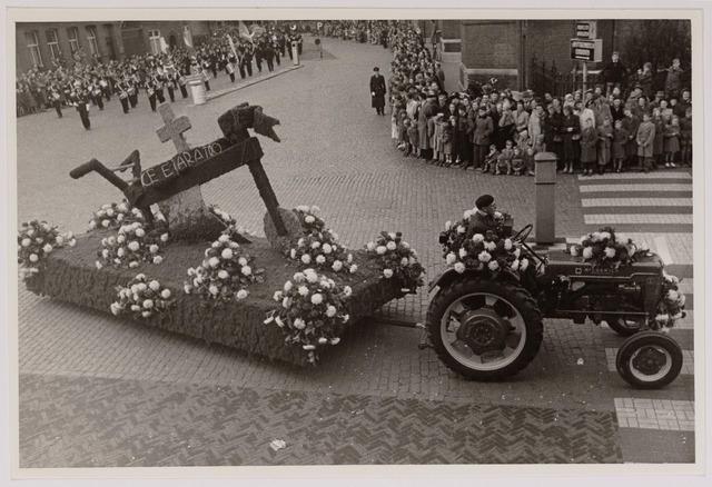 043134 - Wol- en bloemencorso b.g.v. het 10-jarig bevrijdingsfeest. Wagen van de N.C.B. 'Cruce et aratro' met kruis en ploeg. (bij kerk van 't Heike Oude Markt).