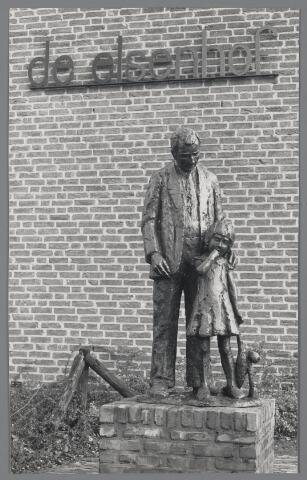 """88911 - In 1908 is de nieuwe Basisschool """"de Elsenhof"""" in gebruik genomen. Rechts aan de voorkant staat dit beeld voorstellende een grootvader die zijn kleindochter, met pop, naar school brengt. Een nog steeds alledaags gebeuren. De maker van dit beeld is N. van Leest."""