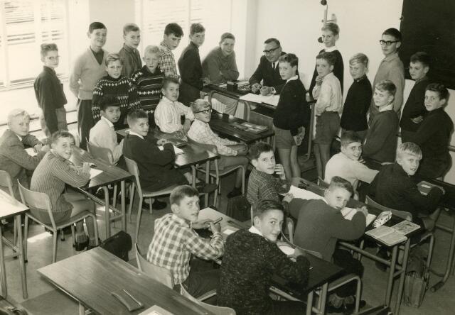 092085 - Klassefoto van klas 1F van de St. PAULUS-HBS, 1963-1964. Achter de tafel docent Nederlands dhr. Cees Pijnenburg.