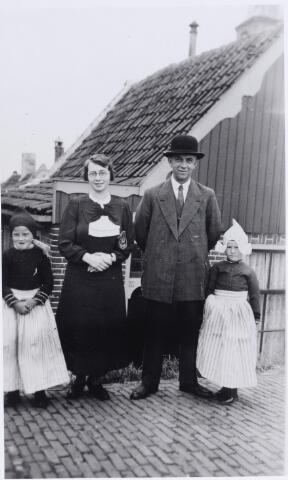 046200 - Toerisme. Bezoek aan Volendam. Tussen de meisjes in Volendammer klederdracht rechts Jan van der Zande, geboren te Goirle op 6 maart 1889 en overleden te Tilburg op 29 januari 1984, en links zijn dochter Maria Adriana (Riet) van der Zande, geboren te Goirle op 18 april 1917. Zij werd 1957 geprofest in het franciscanessenklooster Agnetendal te Arendonk en overleed aldaar in 1999.