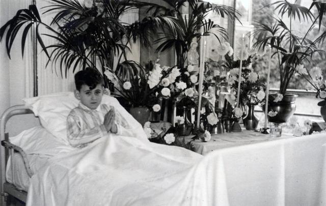 602631 - jongetje op ziekenbed. Naast hem een geïmproviseerd altaar. Mogelijk moest hij de Eerste Heilige Communie doen.