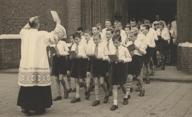 653323 - Parochie Gasthuisring. Tijdens de processie voor de overbrenging van het Allerheiligste vanuit de oude Paterskerk naar de nieuwe kerk van O.L.V. van Altijddurende Bijstand, zingt het jongenskoor