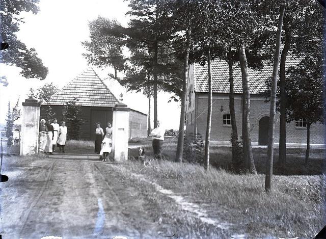 651599 - Mensen en een hond aan het einde van de oprijlaan bij een poort voor de boerderij.  De Bont. 1914-1945.