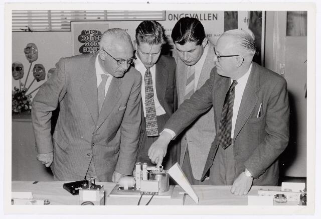 """038922 - Volt. Zuid. Tentoonstelling van de Volt vakliedenopleiding april/mei 1957 in de kantine aan de Voltstraat. Deze kantine was de bovenverdieping van gebouw B. Zie de platte grond in het boekje """"Tussen gloeilamp en hoogspanningstrafo"""" op bldz. 40. Dhr. de Jong, rechts, hoofd werkplaats E.T.Lab. toont een door zijn leerlingen gemaakt werkstuk."""