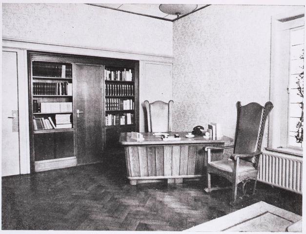 031574 - Interieur. Spoorlaan. N.V. Verzekering-maatschappij Johan de Witt, Tilburg. De werkkamer van de directeur de heer Henricus W.C. van Overbeek (1905-1988). Op de parketvloer een houten bureau met twee klassieke stoelen.