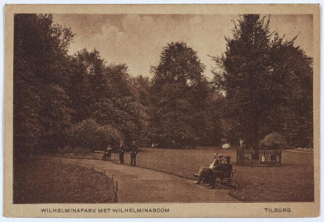 002984 - Wilhelminapark met rechts achter de mannen op het bankje de Wilhelminaboom. Reeds in maart 1898 werd een commissie opgericht ter viering van het kroningsfeest in september. Op 12 september bestonden de feestelijkheden uit een historische optocht, een kindercantate, de plaatsing van een boom in het Wilhelminapark en 's-avonds een vuurwerk in het voornoemde park.   Tijdens de optocht werd gestopt bij het Wilhelminapark om daar de 'Wilhelminalinde' te planten die was uitgezocht door de leden van de plaatselijke afdeling van de 'Maatschappij van Tuin- en Plantkunde'. Bij het planten waren leden van de vereniging aanwezig naast het college van B. &. W., de raadsleden en 'de bereden deelnemers' aan de historische optocht. De eerste spade werd in de grond gestoken door de burgemeester de gekleed was als kamerlid. Na het planten riepen de deelnemers spontaan 'leve koningin Wilhelmina', waarna de historische optocht verder trok. Overigens werd de eerste boom in het park geplant op donderdag 17 maart 1898 door de oudste Tilburger, de 96-jarige H. Wilborts.