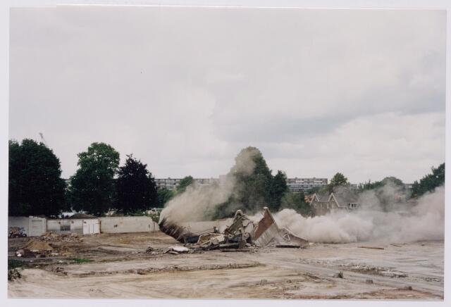 043841 - Het opblazen van de fabrieksschoorsteen op het terrein van de Regenboog aan de Bredaseweg.