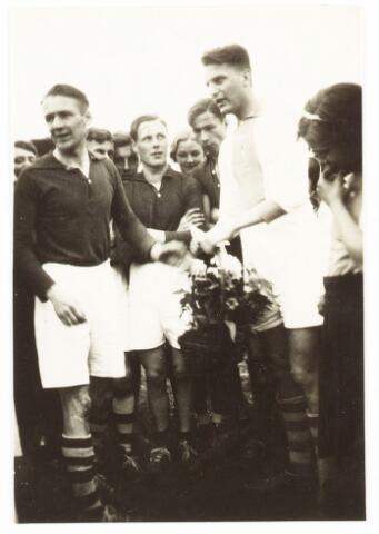 052842 - Sportvereniging Volt afd. korfbal omstreeks 1940. Een lid van Volt, met licht shirt, krijgt of overhandigd een bloemstuk.
