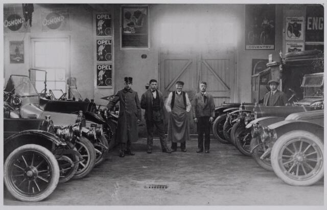040380 - Motorvoertuigen. Interieur van de garage van Th.A.M: Knegtel, handelaar in auto's. Fortdealer. In 1912 gevestigd aan de Spoorlaan samen met Leo Wagemakers. 2e persoon van links Ruts, 2e van rechts Jan Bestens. Huisvesting wagenpark generale staf. 1e garage in 1914.