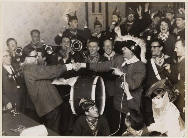 101522 - Carnaval. Leo Willems drukt Jac van Hollenburg de hand tijdens de Smulnarrenbijeenkomst in Central terwijl Ton Kool aan de microfoon de zaak aan de gang houdt