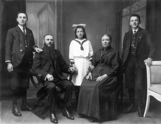 063873 - Familie Van Belkom. Zittend Henricus Marcus van Belkom, geboren te Tilburg op 25 april 1869 en aldaar overleden op 29 juni 1930. Hij was voller van beroep en de eerste suisse van de Besterdse kerk. Naast hem zijn tweede vrouw, Anna Christina Remmers, geboren te Tilburg op 14 februari 1866. Hij trouwde haar te Tilburg op 19 januari 1912. Op de achterste rij de kinderen bij zijn eerste vrouw, Huiberta de Graauw uit Driel. Van links naar rechts: Henricus Johannes Cornelius Maria (Harrie) van Belkom, geboren te Tilburg op 1 september 1904. Hij trad in bij de fraters van Tilburg en kreeg de kloosternaam frater M. Frederik. Hij overleed op Celebes op 2 november 1957. Vervolgens Maria Cornelia Henrica van Belkom, geboren te Tilburg op 5 juli 1908 (zij trouwde wever Josephus A. Koopmans) en Cornelis Josephus Maria (Kees) van Belkom, geboren te Tilburg op 27 september 1905 en aldaar overleden op 9 december 1998 (hij trouwde met Berta H.C. van Noort).