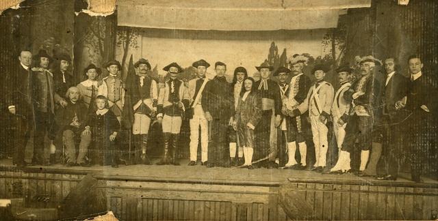 260050 - Amusement. Theater. Groepsfoto van een onbekend toneelgroep op het toneel. Mogelijk is de foto in Goirle gemaakt omstreeks 1915. De mannen dragen waarschijnlijk historiserende achttiende-eeuwse en/of negentiende-eeuwse kostuums, zowel militair als adellijk.