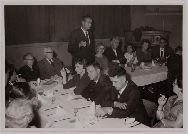 041165 - Vakbeweging. Op 31 augustus 1963 vierde de R.K. Bond Werkmeesters afd. Tilburg het 50-jarig bestaan. 1e een Solemnele H. Mis in de parochiekerk st. Jozef. 2e een feestelijk ontbijt in het parochiehuis aan de Veemarktstraat. 3e herdenkingsbijeenkomst in het Chicago-Theater. 4e Officiële receptie in de zalen van café-restaurant Th. van Broekhoven (Smidspad 42) 5e Feestavonden op 7 t/m 9 september 1963 met uitvoering Operette 'Rumoer in Weinbach' in de Stadsschouwburg met een afsluitend diner. De persoon die de speech houdt is Wim van Hal, meester-timmerman en uitvoerder in de bouw. Links zitten Sjef Smulders (erevoorzitter van de bond) en zijn echtgenote Koosje de Beer.