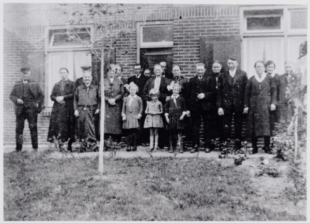 045979 - Gezelschap voor de woning van landbouwer Drik van Dommelen aan de Abcovenseweg 55. Vierde van rechts Hermanus Josephus (Manus) van Dommelen, geboren te Goirle op 17 maart 1887. Twee plaatsen verder naar links zijn vader Hendrikus (Drik) van Dommelen, geboren te Goirle op 11 juli 1855. Twee van de drie meisjes in het midden zijn dochters van Piet van Dommelen, een zoon van Drik, die op 30 april 1925 verhuisde naar Hooge Mierde. Het middelste meisje is Riet van Beurden. Rechts van de boom haar moeder, J.P.J. van Beurden-van den Biggelaar. Zij was de buurvrouw van Drik van Dommelen.