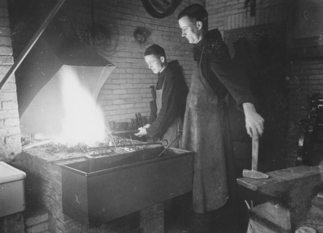 105237 - Monnikenleven Monniken houden het ijzer in het vuur van de smidse. Smederij van de Sint Paulusabdij in Oosterhout rond 1940. Pater B. Schlatmann. Kloosters