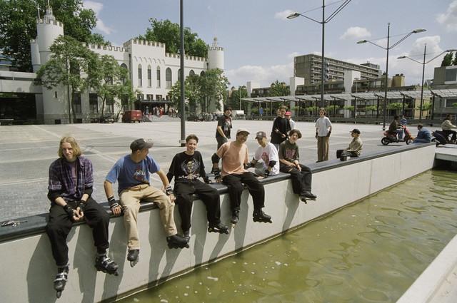 TLB023000866_001 - Skaters op de rand van de waterpartij op het Willemsplein; op de achtergrond het Stadhuisplein en het stadhuis.