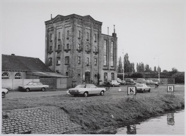 """026089 - Voormalige vormenfabriek aan de Hoevensekanaaldijk.  Op 17 augustus 1868 werd aan Antonie de Kroon, bierbrouwer, een vergunning verleend voor het oprichten van een bierbrouwerij in de wijk Loven, kadastraal B 1517 en 1518, """"onder voorwaarde dat de brouwerij binnen zes maanden na dagtekening van dit besluit in werking moet zijn gebracht"""".  In 1917 verleenden B & W van Tilburg aan C. Poort, bierbrouwer, wonende Bosscheweg 6, een vergunning tot het oprichten van een groentendrogerij met gasmotor in het pand Bosscheweg 8. [De Hoevensekanaaldijk bestond toen nog niet!] Architekt was C.M.B. van den Beld. [Of betreft het hier een verbouwing van een reeds bestaand gebouw? Ik zal dat nog nakijken in het kadaster, RvP.] In 1927 werd aan C.P. van Battum een vergunning verleend tot verbouwing van het pand Hoevensekanaaldijk Oost (ongenummerd) voor de inrichting van een vormenfabriek. In 1940 werd het gebouw in gebruik genomen als kunstwolmalerij van de fa. A. van Grinsven & Zn., Hoevensekanaaldijk Oost 2. In 1945 was het gebouw in gebruik bij de N.V. Gloeilampenfabriek De Backer. In de jaren '50 was de firma Tempofoon (grammofoons) er in gevestigd. Van 1972 tot 1983 werd het gebouw o.m. bewoond door de kunstenaar Wijnand van Lieshout (07/04/1940), die er ook zijn atelier had. Tot begin 1982 was het gebouw eigendom van mevr. De Backer-de Madere. Daarna kwam het in handen van autohandelaar Roskam.  Het gebouw is gesloopt in 1988. Het had toen als adres: Lovensekanaaldijk 120."""