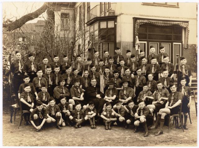 """052939 - Jeugdorganisaties. Scouting. De scoutinggroep Petrus Canisius (parochie Korvel) gefotograffeerd bij de oprichting. In het midden kapelaan Van Kemenade. De groep werd opgericht door kapelaan van Kemenade van de parochie Korvel, die belast was met de jeugdzaken in de parochie. Later werd hij pastoor van Liessel, De oprichting kwam tot stand in 1937 en in 1938 werden de eerste leden geinstalleerd. Als leiders van de verkenners werden de vaandrigs Ed de Grood en L. v.d. Besselaar aangetrokken. De dames Jansen en Van de Bijl kregen de leiding over de welpen. De verkenners werden ondergebracht in het parochiehuis, de welpen op de bovenverdieping van het huis dat stond voor het parochiehuis. In de oorlog werd de groep ontbonden, maar om de onderlinge contacten te behouden werd gestart met een soort turngroep, maar dit werd geen succes. Vaandrig Ed de Grood kwam nu met een plan om onder geleide aan zelfvorming te doen, waarbij de oude gilden model stonden.Zo kwam het St. Paulusgilde tot stand met als voornaamste activiteit het organiseren van zomerkampen o.a. in 1942 naar Malden en in 1943 naar Overasselt. De tocht naar Malden stond onder leiding van """"vader Alcuin""""(kapelaan van Kemenade) en deken Charlemagne (E.M. de Grood). Na de bevrijding werd het St. Paulusgilde ontbonden en ging de scoutinggroep Petrus Canisius weer van start. Op 27 mei 1962 werd het zilveren bestaansfeest van de groep gevierd (zie N.T.C. 24 en 28 mei 1962)"""
