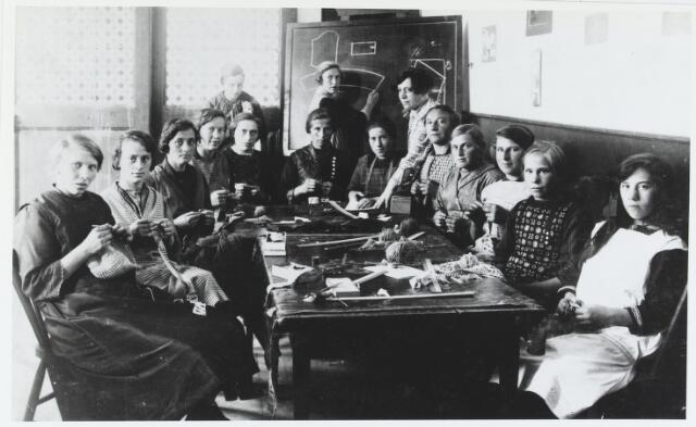055571 - Onderwijs, Naaicursus aan de voormalige armenschool rond 1925. Zittend te beginnen vooraan links: Pietje Simons-Vriens, Marie Dirkx-Verhoeven, Bertha van Gestel-de Bresser, Bertha van Doormaal-Abrahams, Kee Ketelaars-Moonen, Jans van Dooren-Nooijens, Anneke Michels-van Dijck, Jans de Kort, Lies Blankers en Nelleke van Gestel. Links achteraan staan Miet Prinsen en Miet van gils-Verhoeven. Staande bij het bord juffrouw Ambachs.