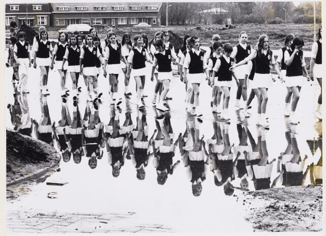 101235 - Sport. Wandelsport. Meisjes in wandeltenue spiegelen zich in de plassen op de weg.