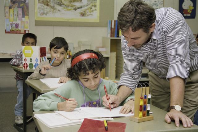 """TLB023000258_001 - Onderwijzer met kinderen in een klaslokaal tijdens de rekenles. Op de voorgrond staat een """"Abacus"""", ook telraam of rekenrek genoemd, en is een mechanisme om sommen en andere wiskundige berekeningen mee uit te voeren. Het is een voorloper van de rekenmachine en de computer. Foto is gemaakt in het kader van de Gemeentelijke Begrotingsspecial 1993."""