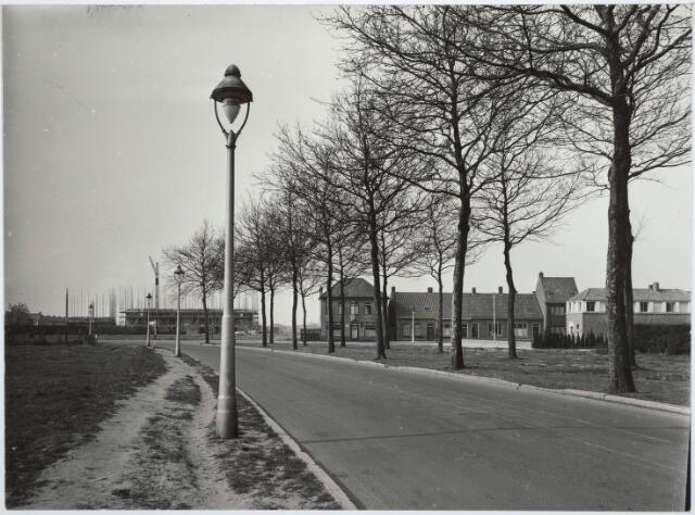 030187 - Ringbaan-West. Van links naar rechts de Berkdijksestraat. In het midden café Franken, rechts apotheek Van Nunen. Op de achtergrond de bouw van de flats langs de Johannes van Zantenstraat. De westelijke rijbaan van de Ringbaan was nog niet aangelegd. Zie ook foto 030171.
