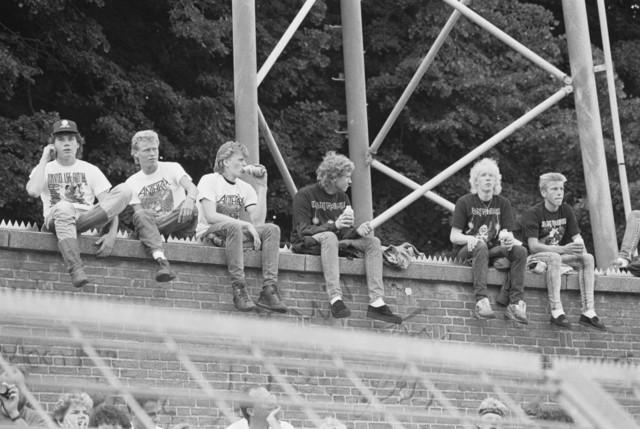 TLB023000010_002 - Bezoekers van het Monsters of Rock festival in het Willem II stadion, zittend op een muur