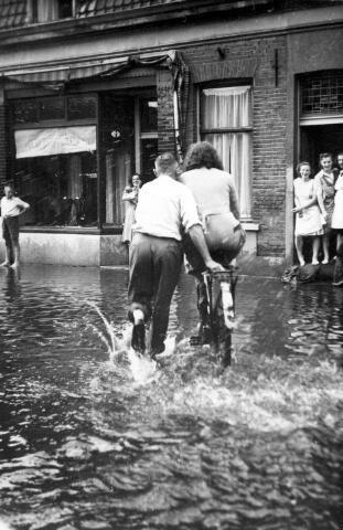 064754 - Wateroverlast zomer 1948 in de Piusstraat. 2 augustus 1948. Tijdens de Tilburgse kermis ontstaat er een zondvloed. Niemand had er op gerekend. Op half vier was de lucht al zwaarder bewolkt dan de rest van de middag. Plotseling begint het regenen, de kermisvierders vluchtten de portieken in met de hoop dat het regenbuitje snel zou overdrijven, de kermispot op zak.  Noodweer breekt uit, knetterende donderslagen en zware regenval. Gemopper in de portieken was het gevolg, in het laagste gedeelte van de stad geen gemopper maar huilende moeders. De putten konden het regenwater niet aan en de kelders liepen vol water. De kinderen vonden het prachtig, schoenen en kousen werden uitgedaan om pootje te baden. Tilburg leek wel op Scheveningen. Zo te zien hebben deze man en vrouw in de Piusstraat ook dolle pret.