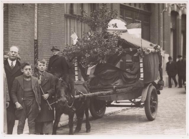042697 - Leden van de Christelijke Jongelingenvereniging poseren op 1 februari 1938 in de Nieuwlandstraat met een versierde kar ter ere van de feesten rond de geboorte van prinses Beatrix