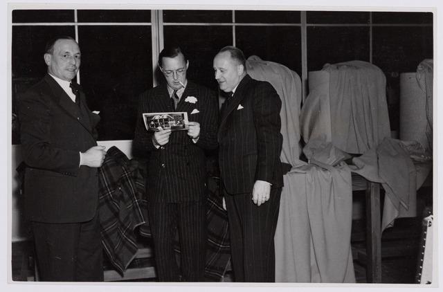 037686 - Textielindustrie. Vol belangstelling bekijkt prins Bernhard een foto tijdens zijn bezoek aan wollenstoffenfabriek H. F. C. Enneking in 1950. Links directeur Hein Enneking sr., rechts diens broer en mede-directeur Frans Enneking sr. Ook beide zonen van de firmanten, Hein jr. en Frans jr., zaten in de directie van het bedrijf