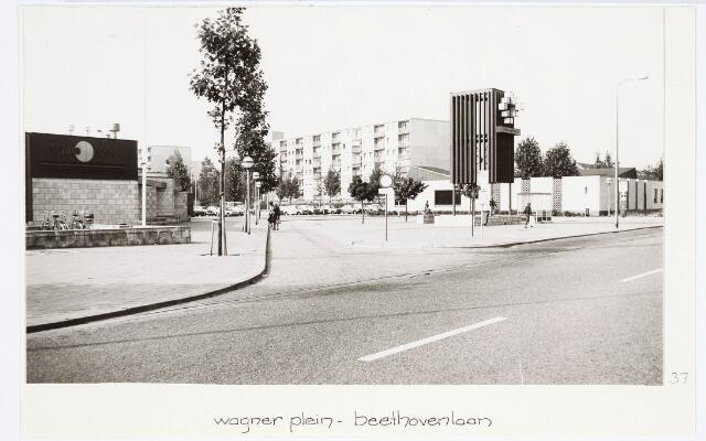 034214 - Het Wagnerplein en de Beethovenlaan met het winkelcentrum en het busstation. Linksvoor Cleanorette en fietsenstalling.