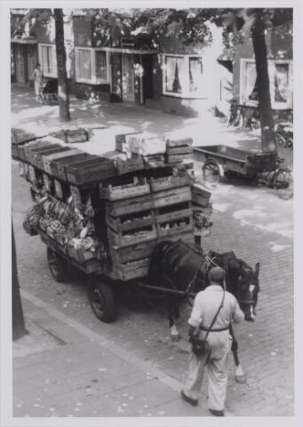 040317 - Een groenteboer met zijn volgepakte kar met paard in de Leenherenstraat. Aan de overkant van de straat een lege bakfiets
