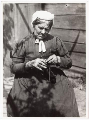 008510 - Vrouw met breiwerk achter haar huis, gefotografeerd door Henri Berssenbrugge (1873-1959) begin 1900.