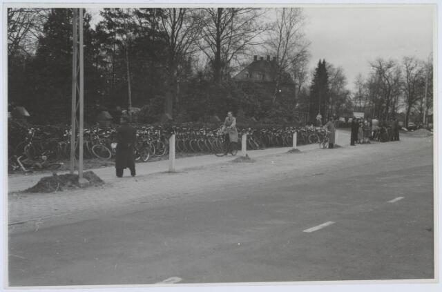 019689 - Fietsenstalling tegenover het sportpark aan de Goirleseweg.. Midden op de achtergrond restaurant Bremhorst, voorheen sociëteit Philharmonie