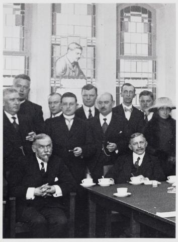 103447 - Bibliotheek.  Een deel van het leeszaalbestuur tijdens de opening in 1922. V.l.n.r.;  staand: P.M. Arts, nn, H. Mannaerts, G. Eras, J. de Louw, J. Horvers, Zittend links de schrijver Frederik van Eeden en rechts Th. Verhoeven, de toenmalige voorzitter.