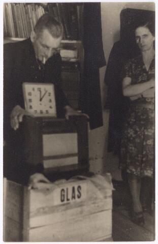 """049833 - Nadat de Duitsers tijdens de Tweede Wereldoorlog alle radio's gevorderd hadden, was het alleen nog mogelijk voor degenen die radiodistributie hadden, om het, door de Duitsers gecensureerde, nieuws te ontvangen. Op het klandestien luisteren naar bijvoorbeeld """"radio Oranje"""" stonden zware straffen. De volgende foto's geven een reconstructie uit 1944 van het klandestien luisteren naar de radio door een aantal bewoners van de Poststraat die zich """"de luistervinken"""" noemden. Het radiotoestel zat in een kist in de zaak van J.J. de Vet, winkelier in medische en orthopedische hulpmiddelen op de hoek Poststraat-Langestraat. Vlak bij het pand van De Vet, in de openbare lagere school aan de Langestraat, waren tijdens de oorlogsjaren Duitsers ingekwartierd die ook de zaak van De Vet bezochten en daar, onder andere voor het aanmeten van speciaal schoeisel, plaatsnamen op de kist, waarin het radiotoestel verborgen zat. Na de bevrijding werden de activiteiten van """"de luistervinken"""" getoond in de etalage van De Vet. Op de foto de heer en mevrouw De Vet met de kist, waarin het toestel verborgen zat.De foto is een reconstructie van de situatie tijdens de Tweede Wereldoorlog."""