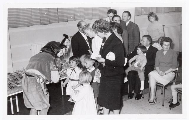 038759 - Volt Oosterhout. Viering van Sint Nicolaas voor de kinderen van het personeel in 1959.Hier enkele kinderen bij het uitreiken van het cadeautje. Fabricage- of productie vond in Oosterhout plaats van april 1951 t/m 1967. Sinterklaas. St. Nicolaas