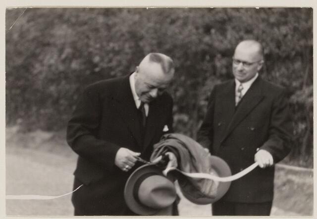 100240 - Opening weg. Burgemeester F.A.J. van Oers knipt het lint door ter gelegenheid van de opening van de weg Oosterhout-Dorst. De heer van Dijk verleent assistentie