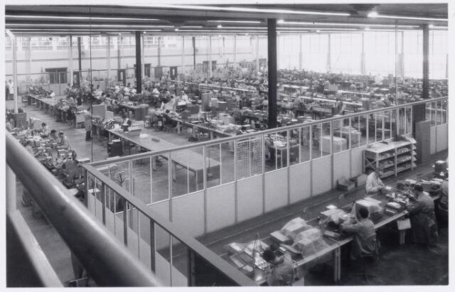 039010 - Volt. Zuid. Condensatoren.  Fabricage. Productie. Een overzicht van de productiehal Z. Deze hal is in gebruik genomen in 1960. In de in 1959 gebouwde hal werd in het najaar van 1959 het 50 jarig bestaan van Volt gevierd. Men sprak nog jaren daarna over de jubileumhal. Hal Z was het 2e gebouw rechts via de ingang Groenstraat. Achteraan boven is door de ramen vaag het hoofdkantoor van Volt zichtbaar.  Links bovenin met witte jas is Kees Huiben.Op de linker rij met kalend hoofd is Kees de Kort. De band vooraan in lichte werkjas is onderbaas Noud van Trier.