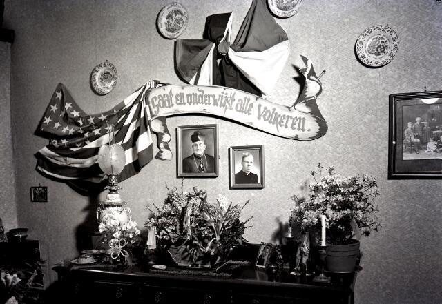 650642 - Schmidlin. Boven het dressoir in het ouderlijk huis van pater Van Grinsven rechts zijn foto. De spreuk boven het dressoir 'Gaat en onderwijst alle volkeren' wijst op zijn vertrek naar de missie.