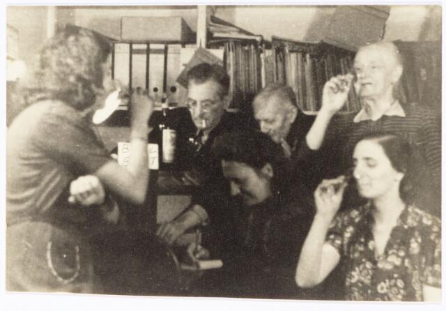 """049835 - """"De Luistervinken"""" uit de Poststraat nemen een borrel op de goede afloop. Van links naar rechts een dochter van het echtpaar De Vet, de heer De Vet, mevrouw R. Zijlmans, de heer en mevrouw Basters en rechts onder mevrouw De Vet.De foto is een reconstructie van de situatie tijdens de Tweede Wereldoorlog."""