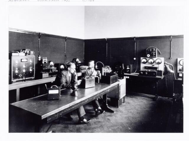 """038539 - Volt. Zuid. De meetkamer in 1933. Links Barend Fruithof, de """"oprichter"""" en afd. chef van het E.T.Lab. (Electro Technisch Lab.)  Later wijzigde deze afdeling zich tot ontwikkelaars van meetapparatuur. Rond 1975 werd dit deel Electrische Ontwikkeling, EO  en in 1988 werd die opgenomen in PS&A ( ProductieSystemen en Automatisering). Ook de kwaliteitsbewaking van de productie van onderdelen was zowel voor Volt als voor buitenfabrieken een van de taken.   Ongeveer in 1975 zijn deze laatste  werkzaamheden onder de namen CQD ( Central Quality Department ), wereldwijd en LQD ( Local Quality Department ) per afdeling verzelfstandigd. Foto uit gedenkboek afscheid van Dhr. Anninga directeur. Voltstraat heette toen Nieuwe Goirleseweg."""