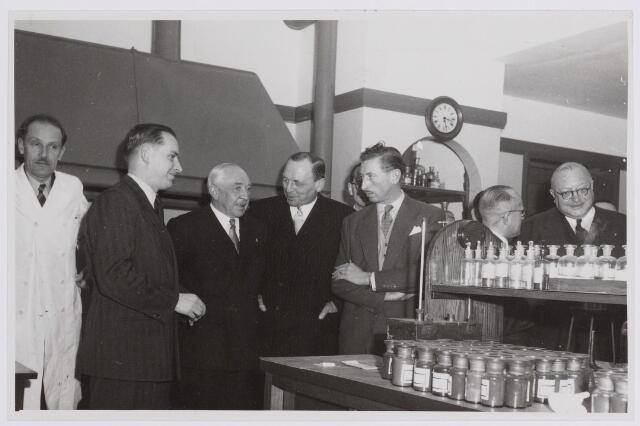037701 - Textiel. Op 13 november 1950 bracht prins Bernhard een bezoek aan Tilburg. Nadat hij op het Paleis-Raadhuis door vertegenwoordigers van ondermeer de Kamer van Koophandel en de Economische Hogeschool op e hoogte was gebracht van de toestand ter plaatse, bracht hij een bezoek aan de Hogere Textielschool en wollenstoffenfabriek H. F. C. Enneking aan de Goirkestraat. Hier is het gezelschap in het laboratorium van het bedrijf