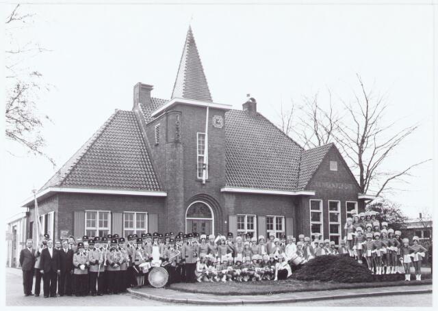 """063473 - De harmonie """"Concordia """" presenteert haar nieuwe uniformen voor het gemeentehuis aan de Raadhuisstraat 56 te Berkel ten overstaan van de burgemeester Jan Meijs, zijn echtgenote en het gemeentebestuur. Staande van links naar rechts C. Pessers (beschermheer), vaandeldrager, Hr. G. Schenkelaars (dirigent)."""