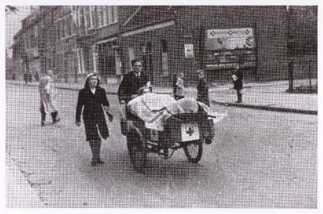 013148 - WO2 ; WOII ; Tweede Wereldoorlog.  Ziekenvervoer in oorlogstijd. Medewerkers van het Rode Kruis vervoeren een gewonde per bakfietsbrancard. Bestuurder is J. van Wanrooij, die zich ook verdienstelijk had gemaakt in het verzet. Foto is genomen op de Bosscheweg ten tijde van de gevechten in septemter - oktober 1944