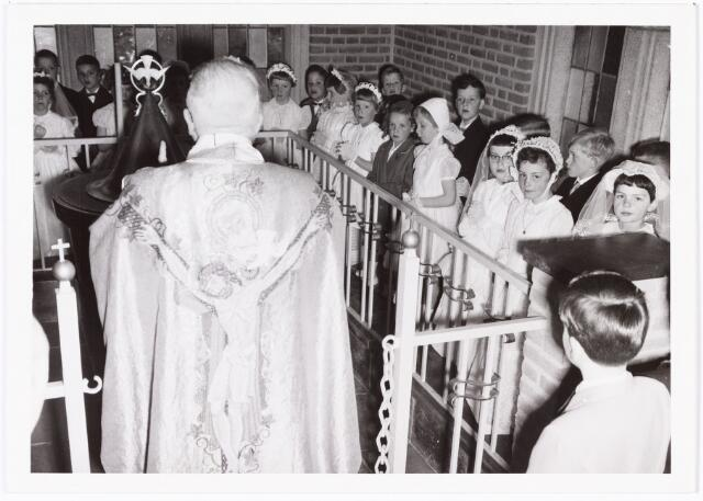009741 - Eerste H. Communie in de nieuwe kerk aan de Gasthuisstraat. Pastoor Karel Janssens met de communiekantjes rond de doopvont.