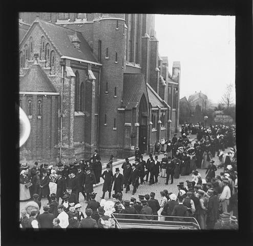 654880 - Stoet met notabelen die langs de Heikese Kerk paradeert.