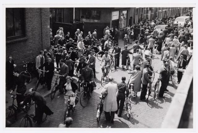 039145 - Volt, Algemeen, Groepsfoto. Medewerkers verlaten de Voltpoort aan de Voltstraat in 1952. Aan de schaduw is te zien dat het omstreeks de middagpauze moet zijn. Die was toen nog van 12.00-13.30 uur.
